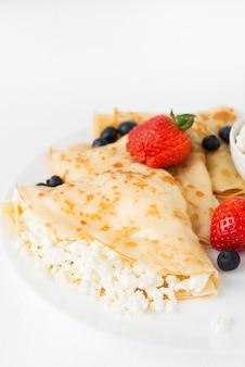 Традиционные русские тонкие блины с творогом и ягодами в тарелке на белом, крупным планом