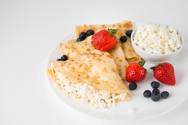 Традиционные русские тонкие блины с творогом и ягодами в тарелке на белом, копией пространства
