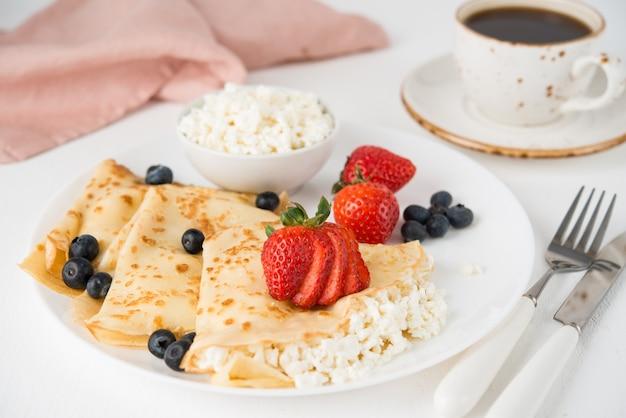 Традиционные русские тонкие блины с творогом и ягодами в тарелке на белом, выборочном фокусе