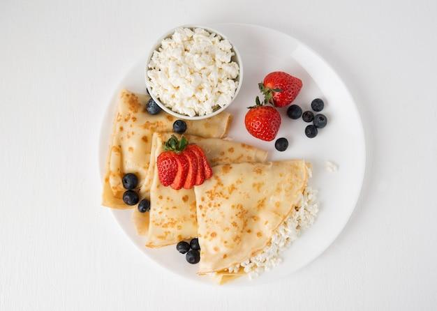 Традиционные русские тонкие блины с творогом и ягодами в тарелке на белом, вид сверху