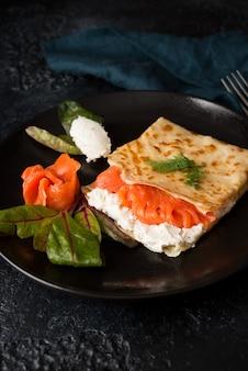 Традиционные русские тонкие блины с начинкой, красной рыбой и сливочным сыром, крупным планом
