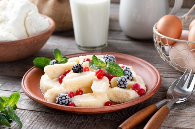 Традиционные русские, украинские творожные вареники «ленивые», подаются с ягодами и мятой на деревянном столе.