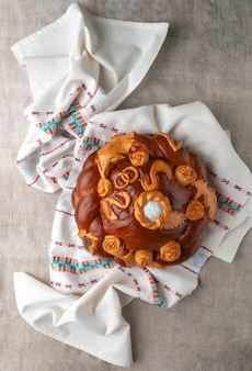 Traditional russian wedding loaf. round shape decorated with flowers and birds. brown. lies on a linen towel. the background is gray. view from above.