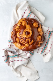 Traditional russian wedding loaf. round shape decorated with flowers and birds. brown. lies on a linen towel. the background is white. view from above.