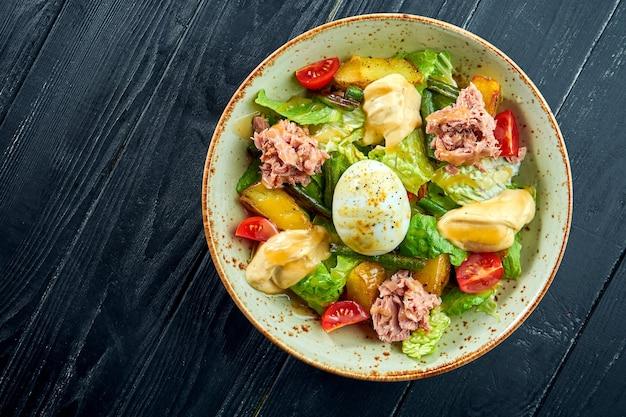 Традиционный салат французской кухни - нисуаз с тунцом, спаржей, помидорами, картофелем и яйцом-пашот подается в миске на черной деревянной поверхности.