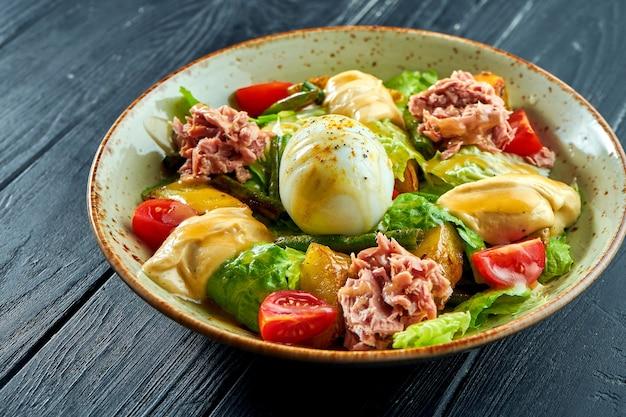 프랑스 요리의 전통 샐러드-참치, 아스파라거스, 토마토, 감자 및 수란을 곁들인 니코 아즈가 검은 나무 표면에 그릇에 담겨 제공됩니다.