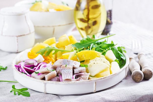 Traditional salad of salted herring fillet, eggs, fresh apples,  red onion  and potatoes.