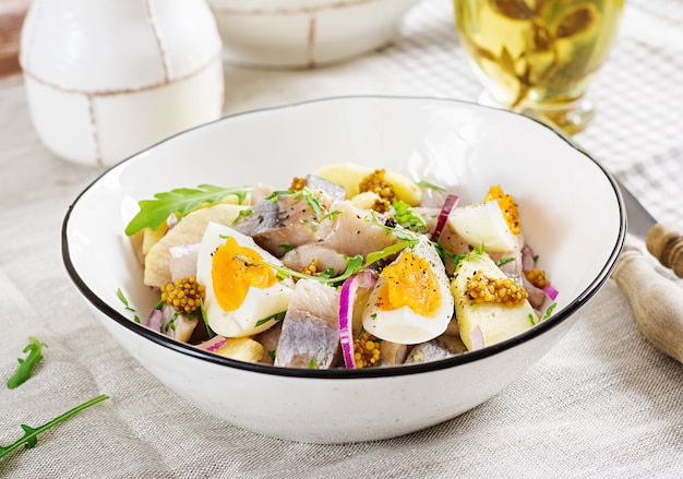 Traditional  salad of salted herring fillet, fresh apples,  red onion  and eggs.
