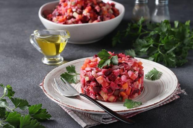 Традиционный салат винегрет из свеклы, картофеля, моркови, фасоли, солений, лука и растительного масла на темно-сером фоне. вегетарианская пища