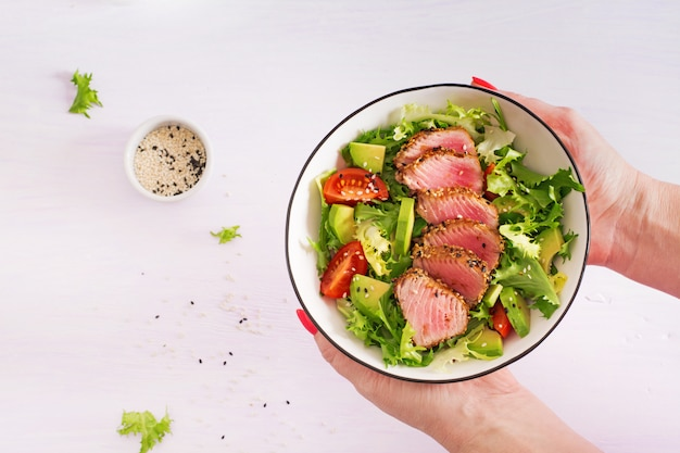Traditional salad with pieces of medium-rare grilled ahi tuna and sesame with fresh vegetable salad