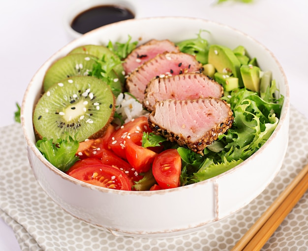 Traditional salad with pieces of medium-rare grilled ahi tuna and sesame with fresh vegetables and rice on a plate.