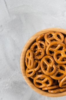 Traditional salty mini pretzels in wooden bowl on a gray backround.