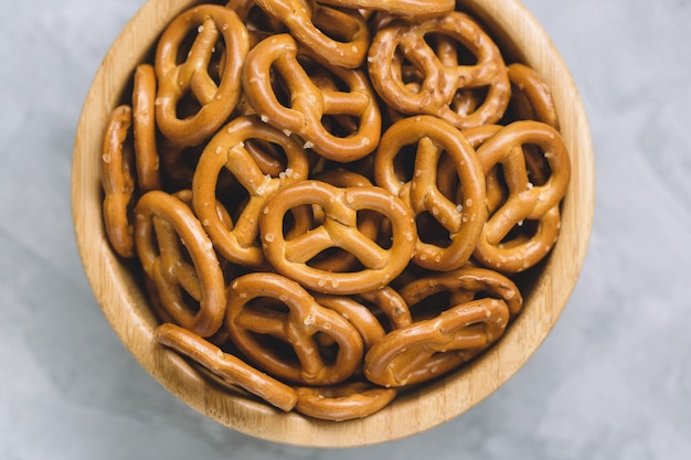 Traditional salty mini pretzels in wooden bowl on a gray .