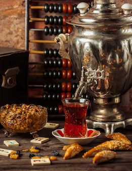 Traditional samovar tea set with variety of snacks, sweets and dry fruits.