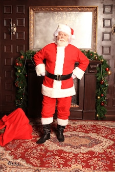 Traditional santa claus standing by the fireplace and christmas tree in a room.