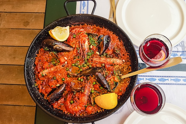 Traditional seafood paella in the fry pan and two glasses of red wine on a wooden old table, top view