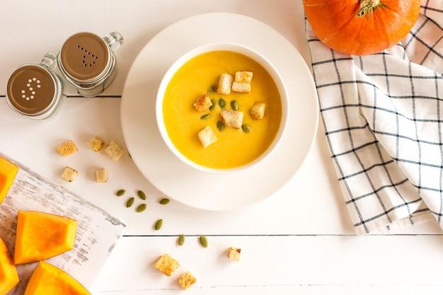 Традиционный сезонный суп из тыквы в миске на деревянном белом фоне.
