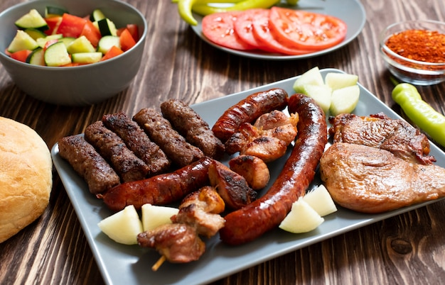 Traditional serbian and balkan grilled meat called mesano meso. balkan barbeque (rostilj) served with serbian salad, hot peppers, bread, tomato, onions, and paprika powder. wooden background. close-up