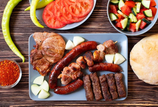 Traditional serbian and balkan grilled meat called mesano meso. balkan barbeque (rostilj) served with serbian salad, hot peppers, bread, tomato, onions, and paprika powder. wooden background. top view
