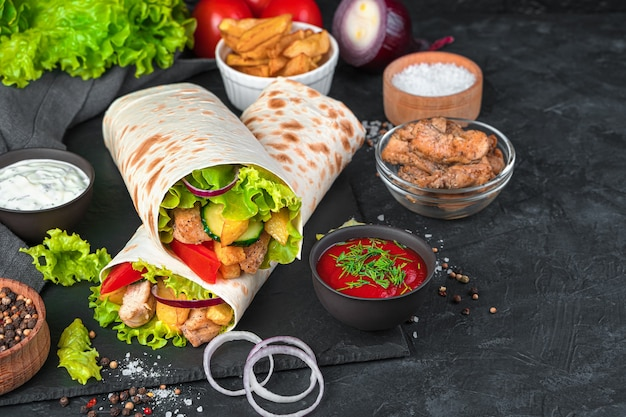 검은 벽에 소스를 곁들인 닭고기와 신선한 야채와 감자 튀김을 곁들인 전통적인 샤와 마. 측면보기, 복사 공간. 패스트 푸드.