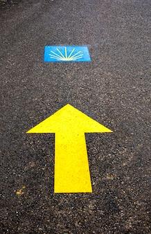 Традиционный знак раковины и желтая стрелка нарисованы на пути. указатель для паломников на пути святого иакова, камино-де-сантьяго-де-компостела, испания