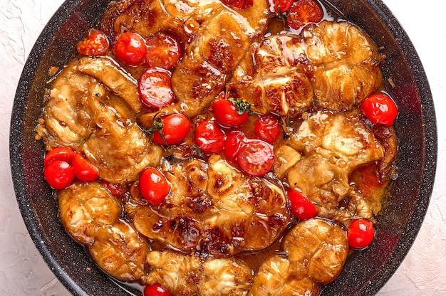 Традиционная сицилийская рыба с помидорами и специями на фоне еды на сковороде крупным планом