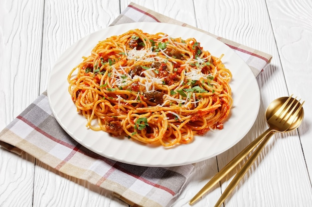 茄子のソテーにトマトソースをかけ、細かく刻んだパルメザンチーズをトッピングした伝統的なシチリアのパスタ料理、イタリア料理、上からの水平方向の眺め、クローズアップ