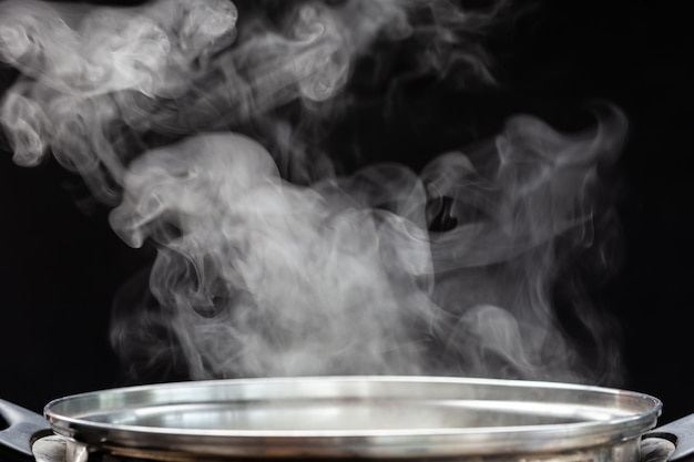 Traditional silver cooking pot with white smoke