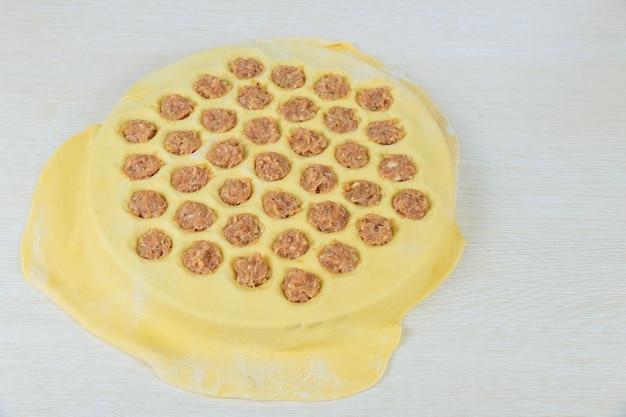 餃子を作る過程で木の板に伝統的なスラブの自家製食品生餃子。
