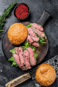 Традиционный нарезанный мясной нарезанный бургер с ростбифом, луком, корнишоном, рукколой и шпинатом