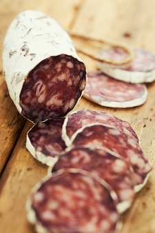 Traditional sliced meat sausage salami on wooden board