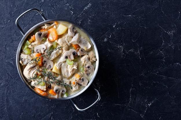 콘크리트 테이블 위의 냄비에 야채와 크림 소스를 곁들인 전통적인 천천히 조리 한 치킨 스튜, 위에서 가로보기, 평평한 바닥, 여유 공간