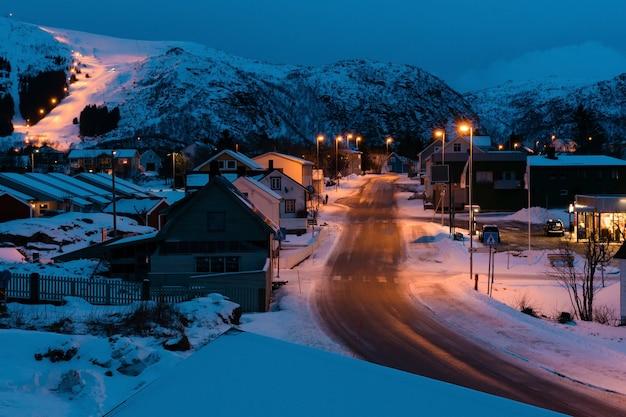 夕方には雪山に囲まれた伝統的な小さなスカンジナビアの村。周りのすべてを照らす街灯。ロフォーテン島で観光客が訪れる美しい場所。