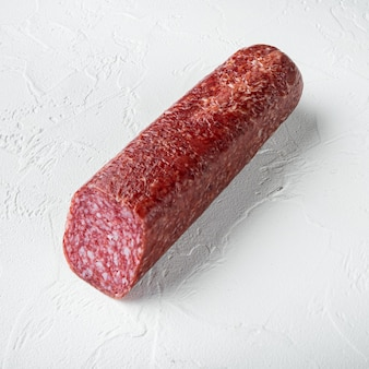 Traditional smoked salami sausage with spices set, square format, on white stone table