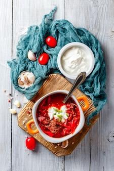 ロシア料理とウクライナ料理のボルシチの伝統的なスープ。オレンジ色のボウルにビートが入った肉のスープ。上面図。