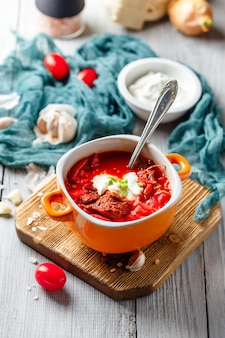 Traditional soup of russian and ukrainian cuisine borsch. meat soup with beets in an orange bowl.