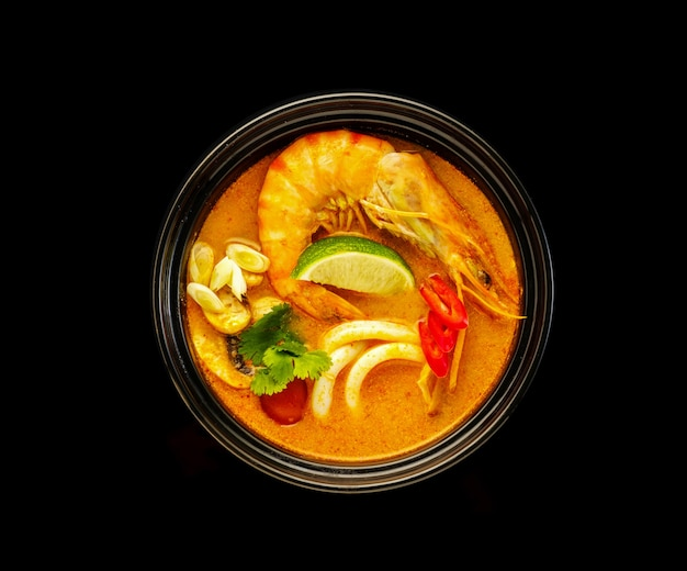 Traditional soup tom yam with tiger shrimps, squids, mushrooms and lime.