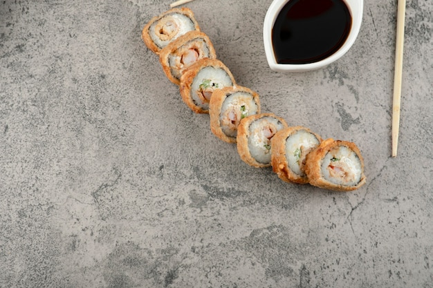 Traditional soy sauce and hot sushi rolls on stone background.