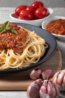 Традиционные спагетти а-ля путанеска на черной тарелке.