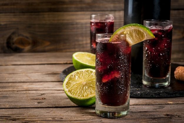 Traditional spanish alcoholic drink cocktail calimocho with wine cola lime juice and ice decorated with pieces of lime