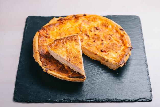 테이블에 그 어두운 접시에 베이컨과 전통적인 스페인 치즈 파이.
