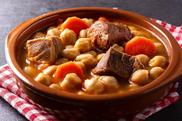 伝統的なスペインのコジードmadrileãƒâ±o。木製のテーブルにひよこ豆のシチュー