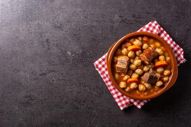 검은 배경에 소박한 그릇에 전통적인 스페인 cocido madrileãƒâ±o