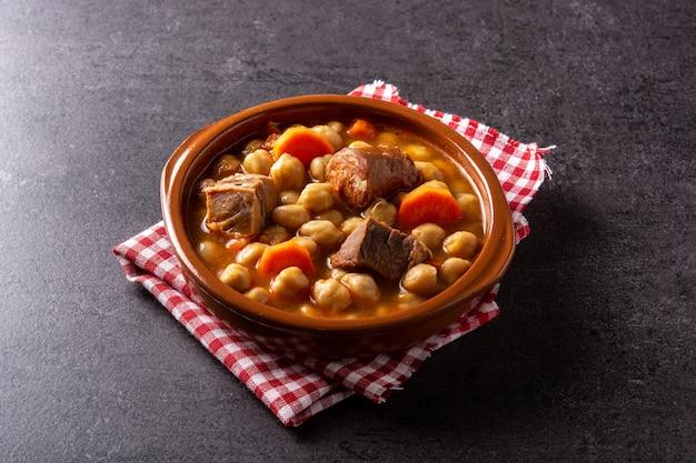 검은 배경에 그릇에 전통적인 스페인 cocido madrileno
