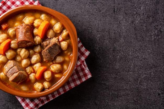 검은 배경에 그릇에 전통적인 스페인 cocido madrilleo