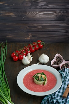 Traditional spanish cold gazpacho soup with mussels. wooden background.