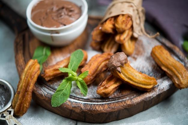伝統的なスペインのデザート。チュロスとチョコレートと粉砂糖