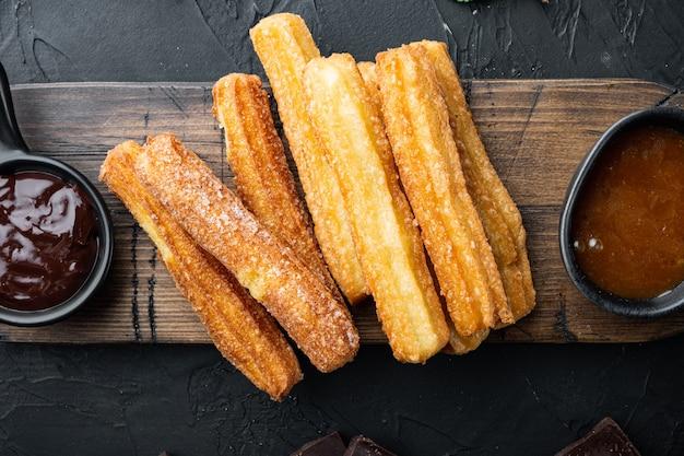 砂糖とチョコレートのセット、黒の背景、上面図フラットレイと伝統的なスペインのデザートチュロス