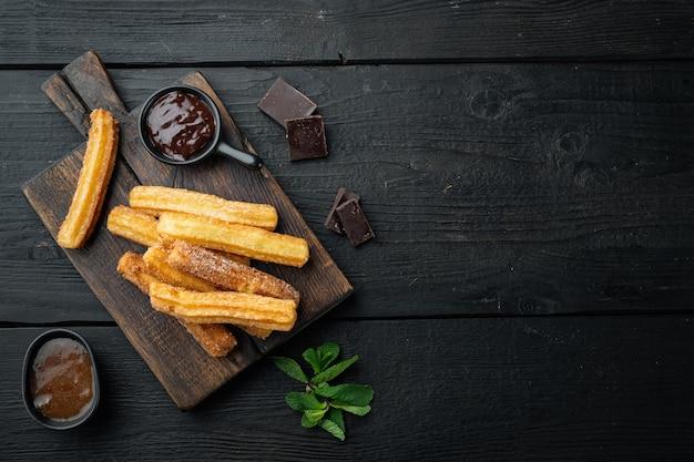 砂糖とチョコレートのセット、黒い木製のテーブルの背景に、テキスト用のスペース、コピースペースを備えた平面図のフラットレイと伝統的なスペインのデザートチュロス