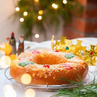 伝統的なスペインのエピファニーケーキ、3人の王、王冠、お祝いの装飾、クリスマスライトを備えたロスコンデレジェス